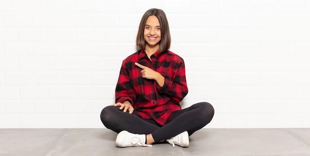 Femme hispanique souriant joyeusement, se sentant heureuse et pointant vers le côté et vers le haut, montrant l'objet dans l'espace de copie
