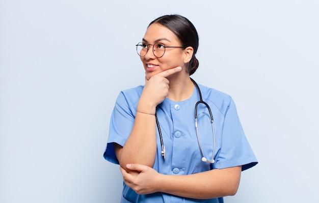 Femme hispanique souriante avec une expression heureuse et confiante avec la main sur le menton, se demandant et regardant sur le côté