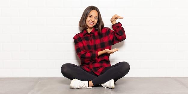 Femme hispanique souriante, se sentir heureuse, positive et satisfaite, tenant ou montrant un objet ou un concept sur l'espace de copie