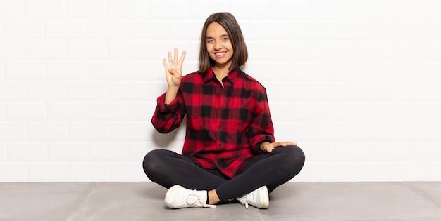 Femme hispanique souriante et semblant amicale, montrant le numéro quatre ou quatrième avec la main vers l'avant, compte à rebours