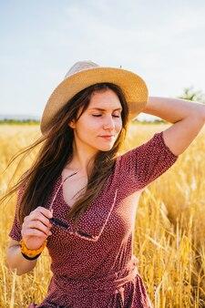 Femme hispanique souriante et tenant son chapeau de paille
