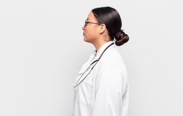 Femme hispanique sur la vue de profil cherchant à copier l'espace devant, à penser, à imaginer ou à rêvasser