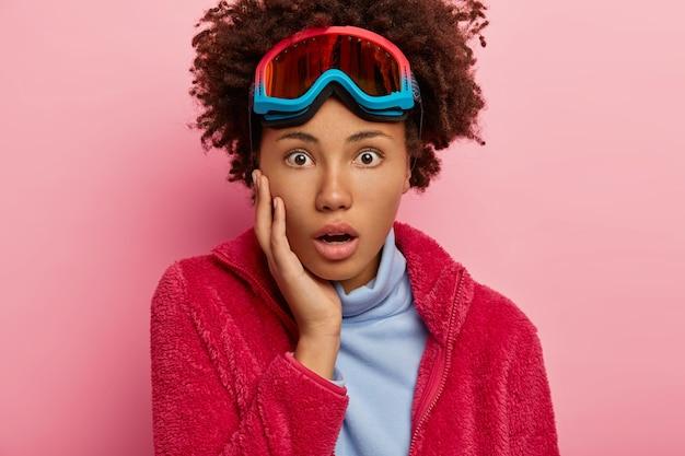 Femme d'hiver impressionnée porte des lunettes pour le snowboard, un pull rouge et un col roulé bleu, regarde avec choc, pose sur fond rose