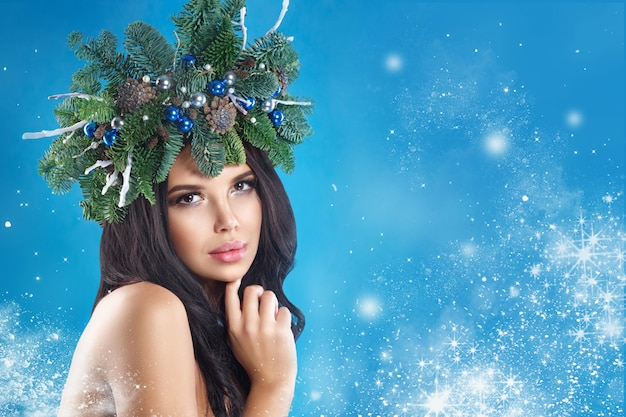 Femme d'hiver de noël. belle coiffure de nouvel an et arbre de noël vacances et maquillage.
