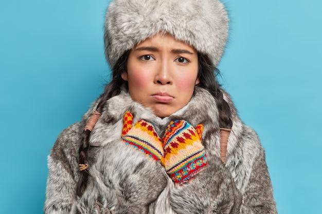 Femme d'hiver regarde tristement à l'avant se sent froid habillé en chapeau de fourrure grise et manteau chaud mitaines tricotées habillées pour l'hiver isolé sur mur bleu