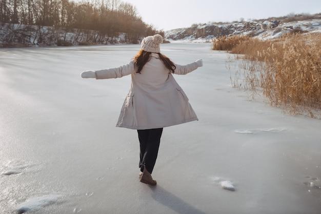 Femme d'hiver s'amusant à l'extérieur sur la nature