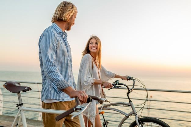 Femme et homme amoureux voyageant à vélo au coucher du soleil sur la mer