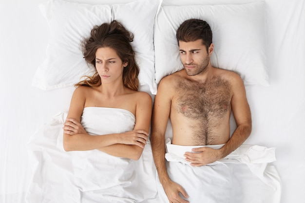 Femme et homme assis dans le lit vue de dessus