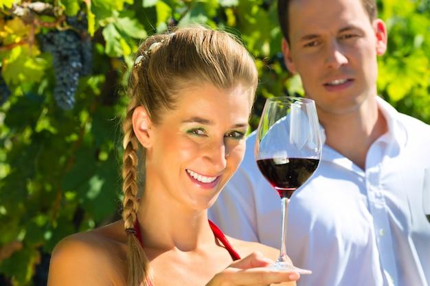 Femme et homme assis sous la vigne et buvant
