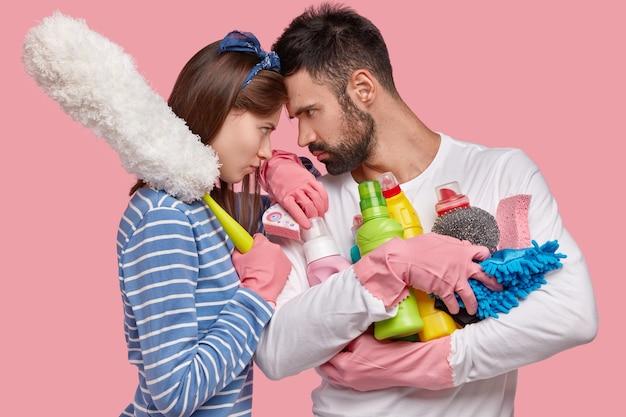 Une femme et un homme en colère se touchent le front, s'accordent à dire qui devrait nettoyer la maison cette fois, regarder avec irritation les yeux, porter des vêtements domestiques, tenir des détergents
