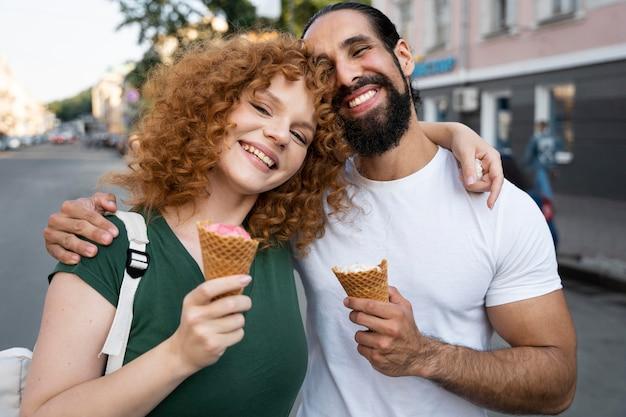 Femme et homme de coup moyen avec de la crème glacée