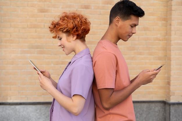 Femme et homme de coup moyen avec des téléphones