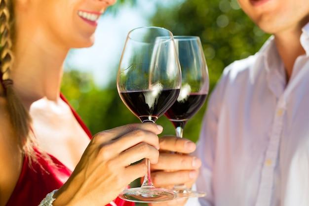 Femme et homme dans un vignoble buvant du vin