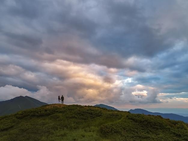 La femme et l'homme debout sur la montagne avec une vue pittoresque