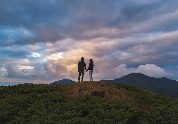 La femme et l'homme debout sur la montagne
