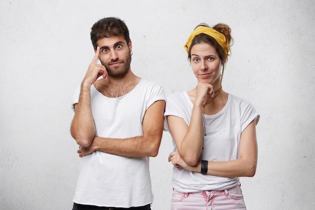 Femme et homme debout près de l'autre ayant des expressions pensive essayant de trouver une solution