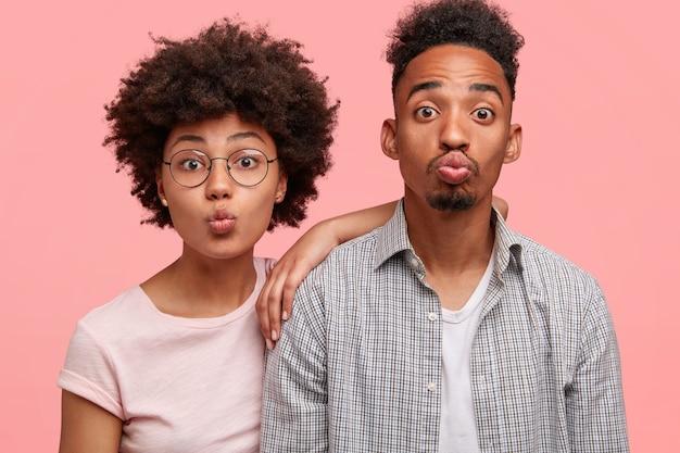 La femme et l'homme drôles garde les lèvres rondes, font la grimace, se tiennent côte à côte, habillés avec désinvolture