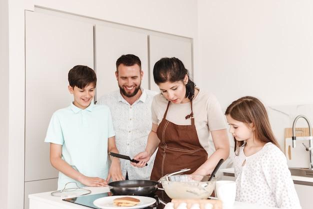 Femme et homme avec des enfants heureux 8-10 cuisiner ensemble et faire frire des crêpes sur une cuisinière moderne dans la cuisine à la maison