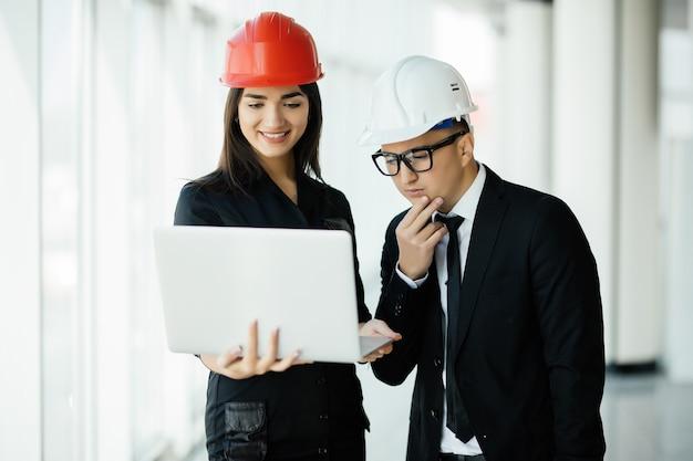 Femme et homme entrepreneur et architecte à hemlet lors d'une réunion d'affaires, regardant l'ordinateur portable sur les plans de construction