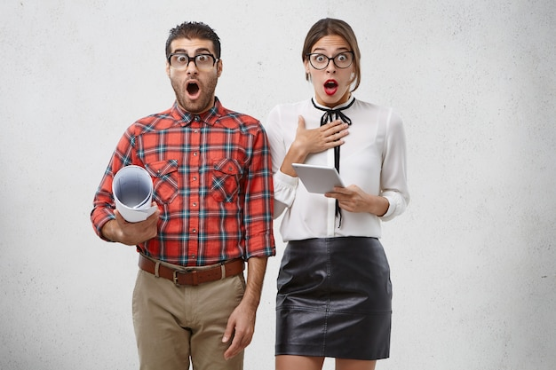 La femme et l'homme étonnés regardent avec le souffle coupé et la bouche largement ouverte