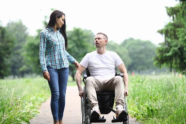 Femme et homme en fauteuil roulant à pied dans le parc et parler