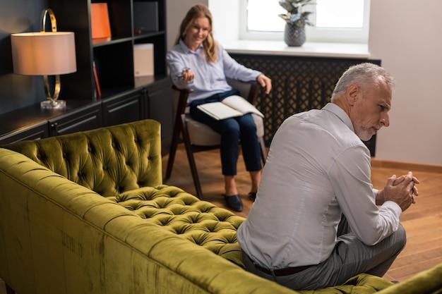 Femme et homme. femme blonde avec un bloc-notes sur ses genoux en souriant