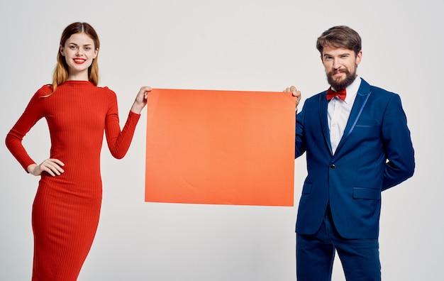 Femme et homme avec une feuille de papier rouge et une maquette de publicité