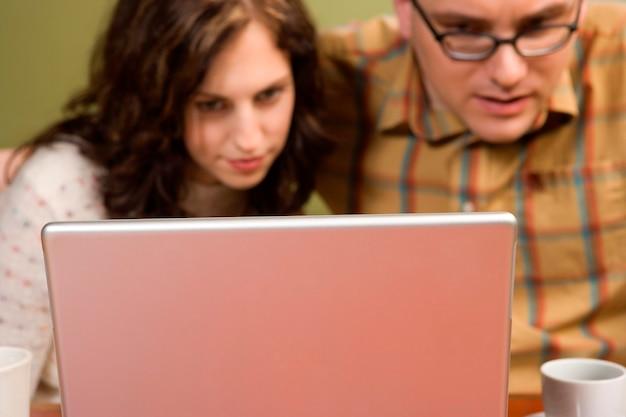 Femme et homme fixant un ordinateur portable