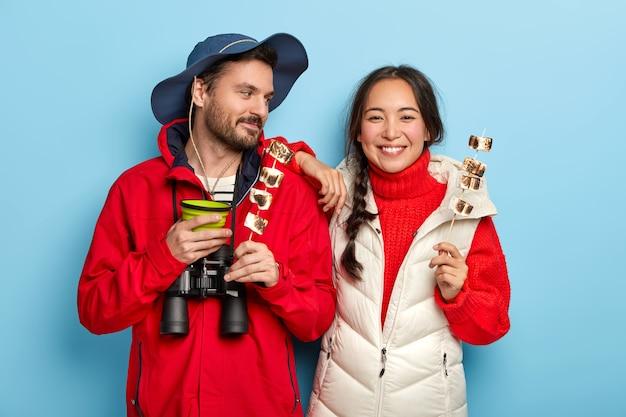 Une femme et un homme heureux passent du temps libre dans la nature, apprécient les activités de camping, tiennent de la guimauve rôtie, boivent du café, prennent un snak et boivent ensemble, habillés de vêtements décontractés