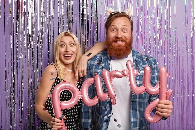 Une femme et un homme insouciants joyeux tiennent des ballons, ce qui signifie fête, venez à l'événement festif