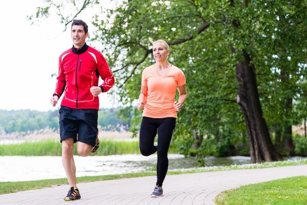 Femme et homme jogging sur chemin de terre dans les bois ensemble