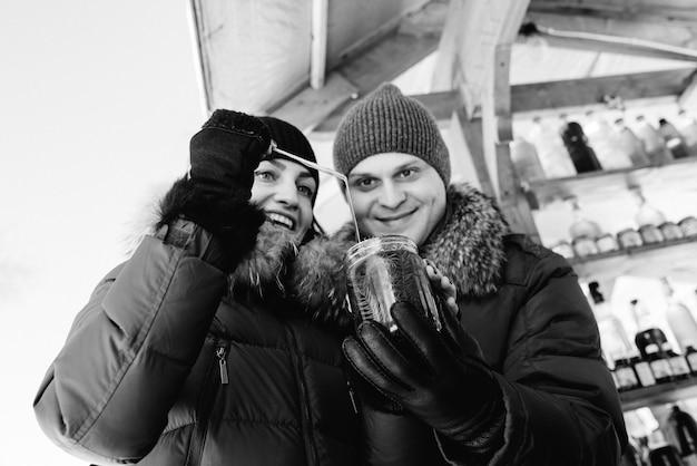 Une femme et un homme joyeux en vêtements d'hiver chauds au marché essaient du miel et des boissons