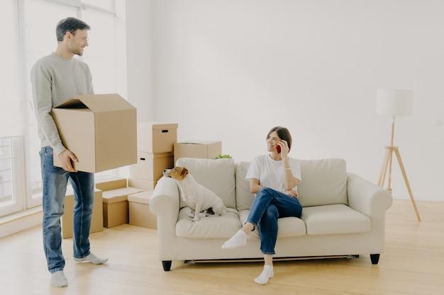 Femme et homme, locataires de biens immobiliers, posant dans un salon vide, femme assise sur un canapé au milieu de la pièce