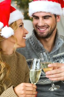 Femme et homme avec des lunettes de champagne regardant dans les yeux les uns des autres
