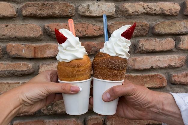 Femme et homme main tenant trdelnik avec de la crème glacée dans le vieux tbilissi. photo de haute qualité