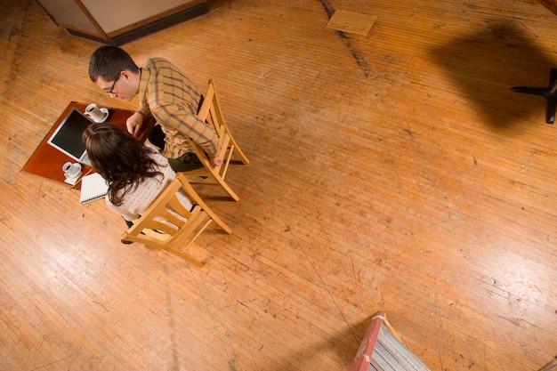 Femme et homme avec ordinateur portable et ordinateur portable dans une pièce vide