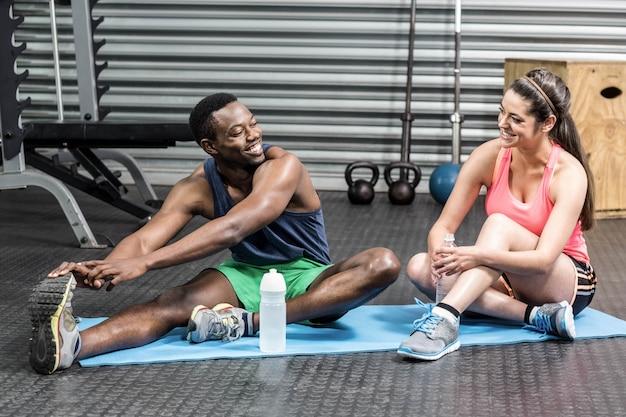Femme et homme parlant et s'étendant sur une serviette de sport au gymnase de crossfit