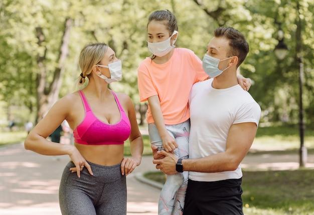 Femme, homme et petite fille marchant dans le parc