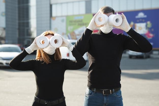 Une femme et un homme portant un masque anti-coronavirus tiennent de gros rouleaux de papier toilette
