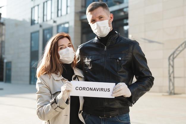 Une femme et un homme portant des masques médicaux de protection tiennent une pancarte