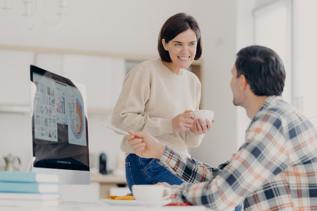 Une femme et un homme positifs discutent du paiement des factures de services publics pendant la pause-café, l'homme pointe sur l'écran de l'ordinateur, affiche des graphiques et des diagrammes et travaille à domicile dans un espace de coworking. collaboration