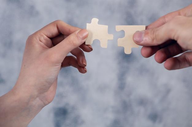 La femme et l'homme relient des pièces de puzzle