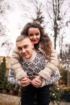 Une femme et un homme se tiennent près de l'arbre de noël, ils sont heureux, l'humeur du nouvel an