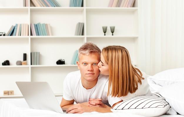 Femme et homme séjournant avec leur ordinateur portable au lit
