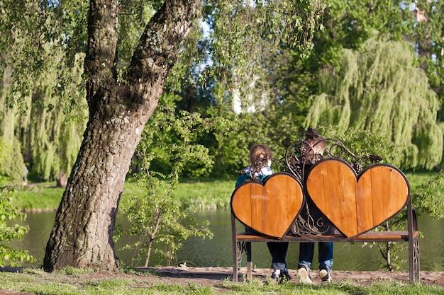 Femme et homme sont assis sur un banc avec deux grands coeurs