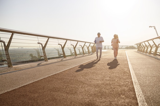 Une femme et un homme supérieurs positifs avec des bouteilles courent le long de la passerelle en soirée d'été