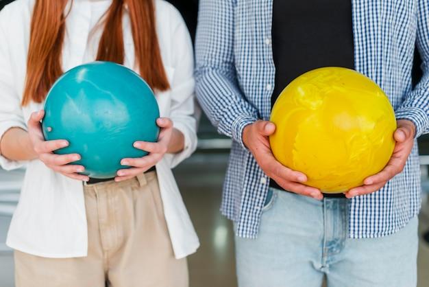 Femme et homme tenant des boules de bowling colorées