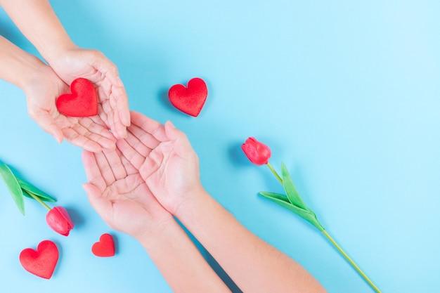 Femme et homme tenant coeur sur bleu clair