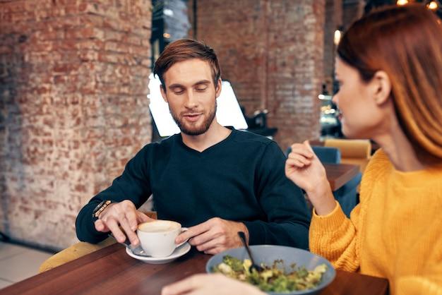 Femme et homme en train de manger au restaurant repas de salade tasse de café