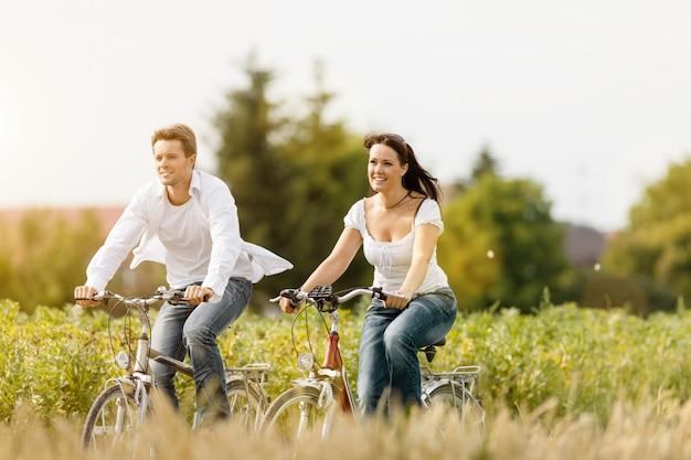 Femme et homme à vélo en été